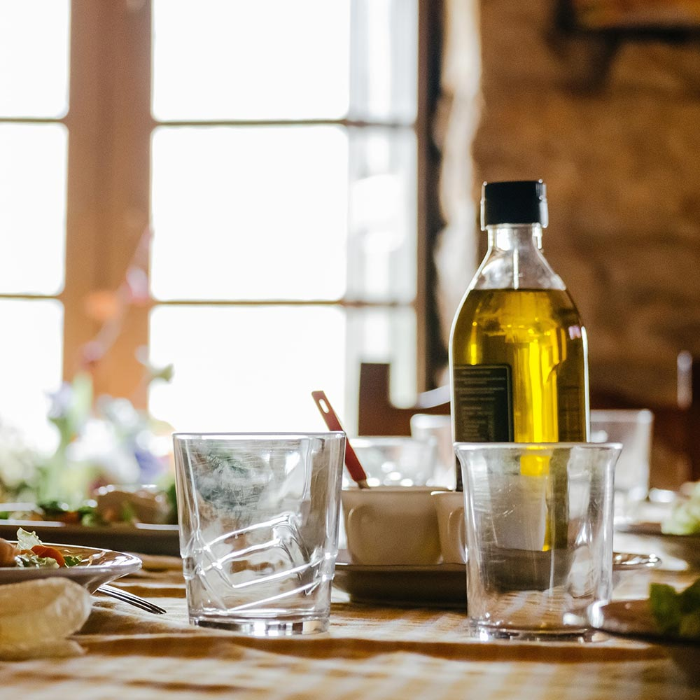 Notos Olivenöl auf rustikalem Tisch abgefüllt in eigene Flasche